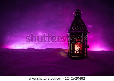 Christmas lantern on snow at night. Festive dark background. New Year's still-life postcard lamp covered in snow with glowing candle at night. Holiday concept. Artwork #1242620482