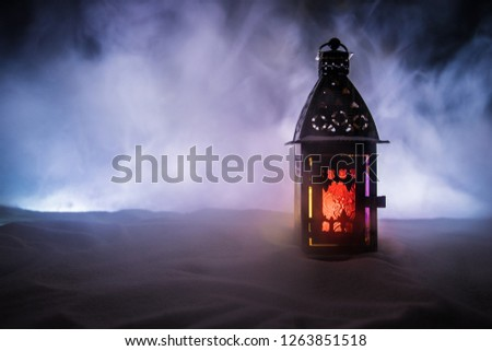 Christmas lantern on snow at night. Festive dark background. New Year's still-life postcard lamp covered in snow with glowing candle at night. Holiday concept. Artwork #1263851518