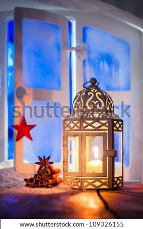 Christmas lantern with a glowing candle burning in a window illuminating dried seasonal spices with copyspace