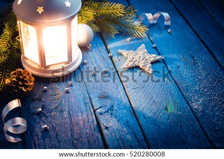 Christmas Lantern with decorations on blue wooden background. Studio shot #520280008