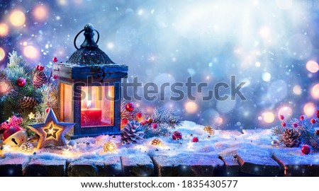Photo of  Christmas Lantern With Fir Branch and Decoration On Snowy Table - Defocused Background