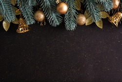 Christmas layout with Christmas trees, gold baubles and bells on a black background with copy space. Top view composition for new year winter greetings