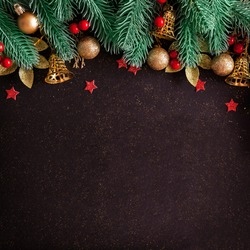 Christmas layout with pine tree, gold baubles and bells, red stars on black background with copy space. Top view composition for new year winter greetings