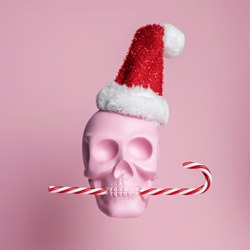 Christmas layout with pink skull wearing Santa's cap and biting candy cane on bright pink background. Minimal New Year's seasonal concept. Holiday greeting card.