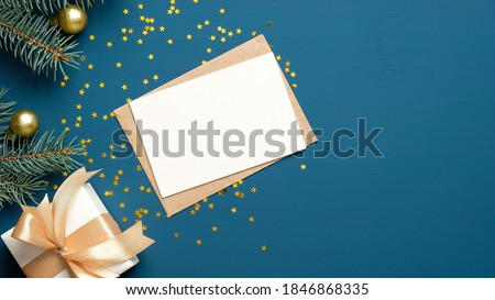 Christmas letter envelope with blank paper card, white gift box with golden ribbon bow, fir branches decorated balls on dark blue background. Flat lay, top view. Letter to Santa Claus concept.
