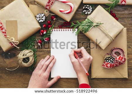 Christmas letter writing on paper on wooden background with decorations