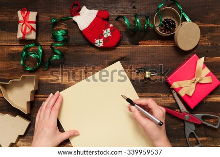 Christmas letter writing on yellow paper on wooden background with decorations