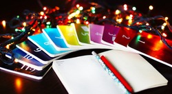 Christmas light bulbs shining with twelve colourful small diaries. Open white page with pen and pencil for planning new year's goals and wishes.