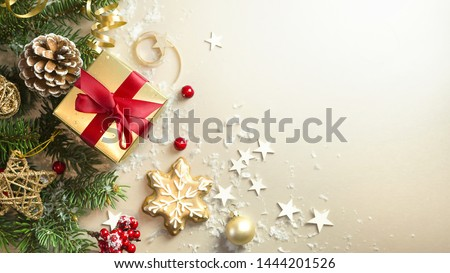 Christmas light gold background with beautiful Golden gift box with red ribbon, fir branches, cones, stars, Christmas cookies, top view, copy space.