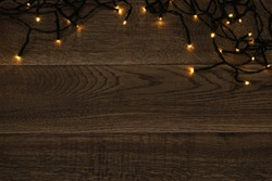 Christmas Light on Wooden Background Top View with Copyspace. Garland Lights on Vintage Wood Texture for New Year Frame or Xmas Mockup