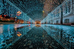 Christmas light tunnel reflected in the puddle. Holiday background. night photography