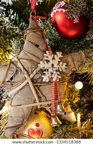 Christmas lights, baubles, stars and other seasonal decorations on a snow frosted xmas tree #1334518388