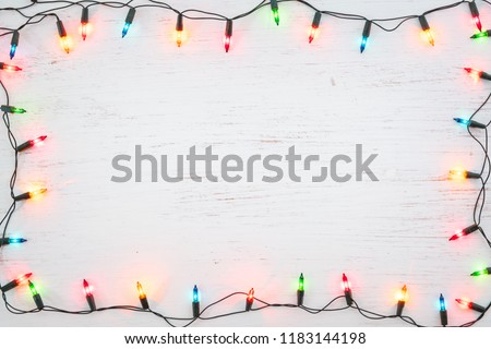 Christmas lights bulb frame decoration on white wood. Merry Christmas and New Year holiday background. top view #1183144198