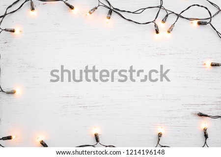 Christmas lights bulb frame decoration on white wood. Merry Christmas and New Year holiday background. top view - Shutterstock ID 1214196148