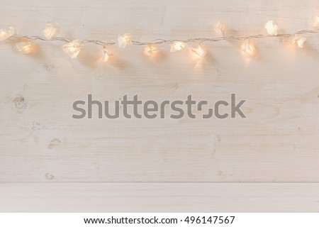 Christmas lights burning  on a white wooden background. Xmas background.