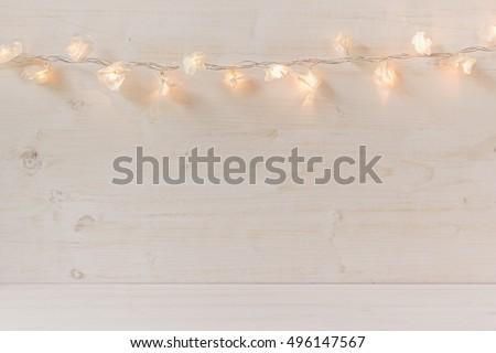 Christmas lights burning  on a white wooden background. Xmas background.
