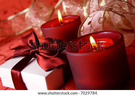 Christmas lights - celebration table (two candles and christmas gift-box on red background)