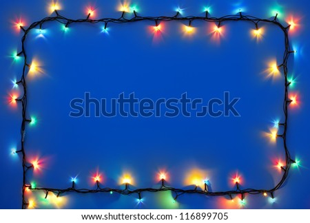 Christmas lights frame on dark blue background with copy space.Decorative garland