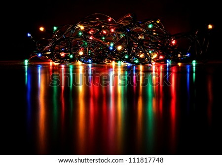 Christmas lights on a tree with a beautiful reflection and black background