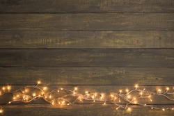 Christmas lights on a wooden background. Copy space for a greetings