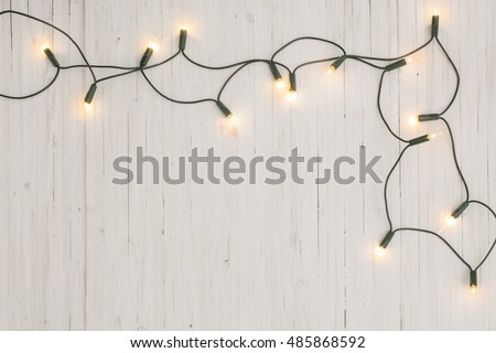 christmas lights on white wooden background