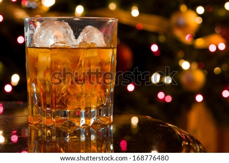 Christmas Liquor Cocktail in a Crystal Glass on a Reflective Table with Christmas Lights Out of Focus in the Background