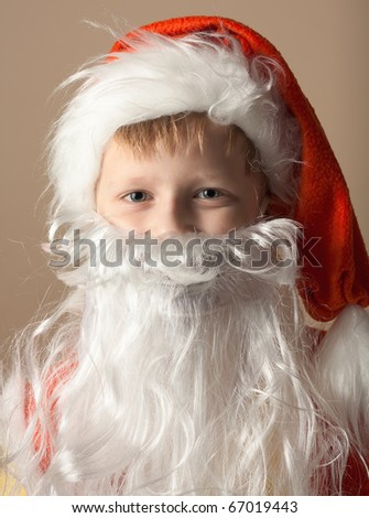 Christmas. Little boy in Santa Claus suit with beard