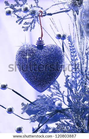 Christmas love. Heart ornament hanging on a branch