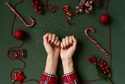 Christmas manicure. Red nails, hands in checkered shirt on green background with red christmas baubles as frame.