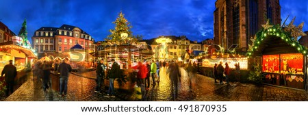 Christmas market in Heidelberg, Germany, a panorama shot at dusk showing illuminated kiosks, architecture and blurred people