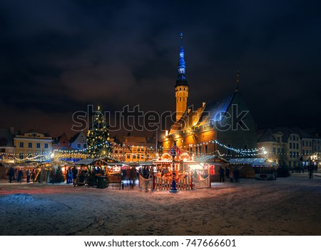 Christmas market in the town hall square in Tallinn. Holiday garlands and decorated Christmas tree in the old town. Trade tents with Christmas gifts and souvenirs.  Winter Estonia.