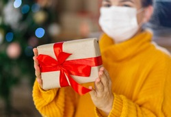 Christmas mask congratulations. Portrait woman wearing yellow sweater in medical mask, giving gift present box with red ribbon,christmas tree bokeh on background