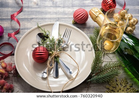 Christmas meal table setting design, flat lay. Empty plate, glass, cutlery, bottle of champagne and decorations. Golden snowflake and berries. Red baubles, green fir-tree branch