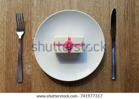 Christmas meals table setting - Pink ribbon gift box on white plate with knife and fork   #741977317