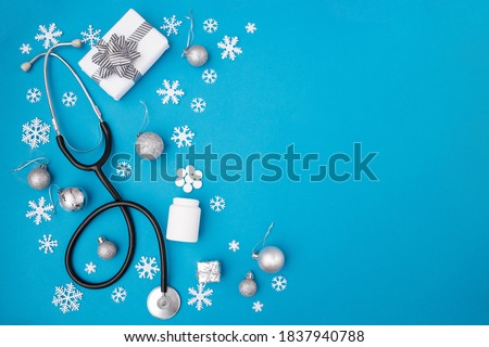 Christmas, medicine greeting card. Christmas decorations, pills on a blue background. Medical concept. Copy space, flat lay.