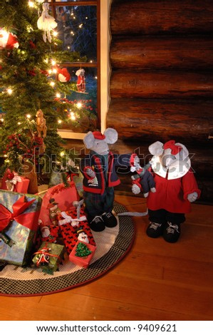 Christmas mice by an old fashioned looking christmas tree in log cabin