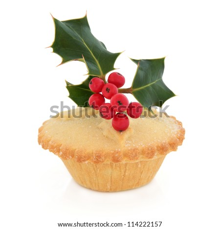 Christmas mince pie with holly and red berry leaf sprig over white background.