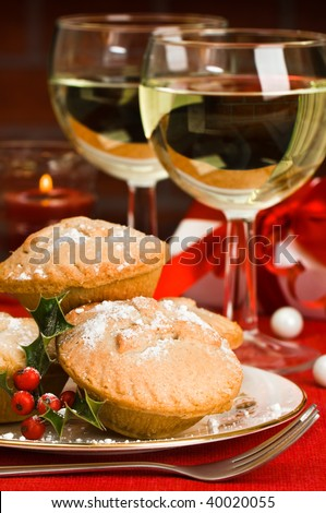 Christmas mince pies with glasses of white wine and decorated gift in background with lit candle