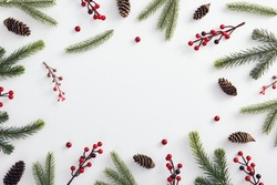 Christmas minimal concept - christmas composition made of evergreen tree branch, pinecone and red berries. Frame composition with copy space. Flat lay, top view. Holiday decoration. Abstract template.