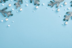 Christmas minimal concept - Christmas composition with snowy fir branch and white bauble. Horizontal top composition, flat lay, view from above. Pastel blue background with copy space