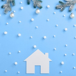 Christmas minimal concept - Christmas composition with snowy fir branch and white bauble. Square composition, flat lay, top view. Classic blue background with white paper home silhouette
