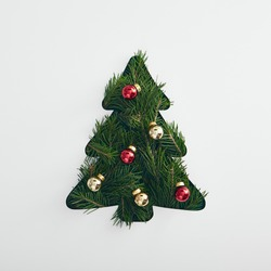 Christmas minimal concept - creative christmas tree made from evergreen branch and bauble. Mockup with green christmas tree flatlay on white background for concept design. Xmas tree geometric shape.