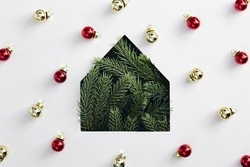 Christmas minimal concept - simple house silhouette made of christmas tree branch with bauble on white background. Flat lat, top view. Minimal house concept. Creative minimal. Holiday concept.