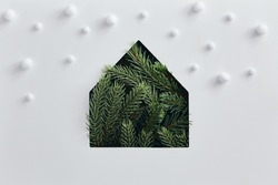 Christmas minimal concept - simple house silhouette made of christmas tree branch with snowfall. Flat lat, top view. Vintage rustic mockup with green tree pine house. Winter background. Christmas snow