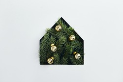 Christmas minimal concept - simple house silhouette made of christmas tree branch with yellow bauble. Flat lat, top view. Tree pine house in abstract style on white background. Christmas background.