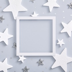Christmas minimal mockup - monochrome layout with white and silver star. Square composition, flat lay, top view. White paper frame. Copy space. Layout mockup.