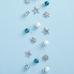 Christmas minimal mockup - white, glass and blue balls, snowflakes and stars confetti on blue background. Square composition, flat lay, top view. Design template. Christmas card concept.