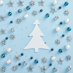 Christmas minimal mockup - white, silver and blue balls, snowflakes and stars confetti on blue background. Square composition, flat lay, top view. White paper christmas tree silhouette