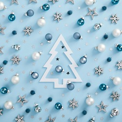 Christmas minimal mockup - white, silver and blue balls, snowflakes and stars on blue background. Square composition, flat lay, top view. Cold monochrome layout with paper christmas tree silhouette