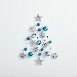Christmas minimalist mockup - shape of xmas tree from blue bauble, silver snowflake and star on white background. Square layout, flat lay, top view. Happy new year and merry christmas.